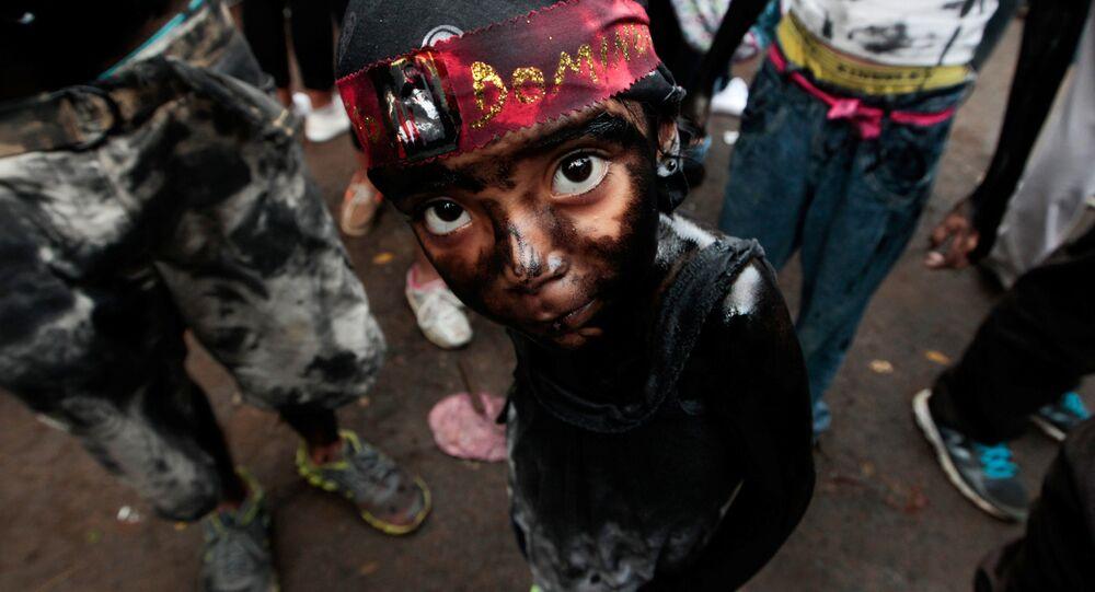 A girl covered in motor oil takes part in the festivities honouring the capital's patron saint Santo Domingo de Guzman in Managua, Nicaragua