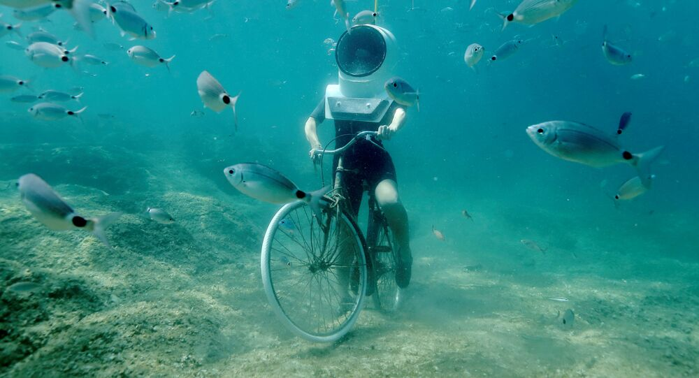 A woman dives and pretends to ride a bike in Underwater Park in Pula, Croatia