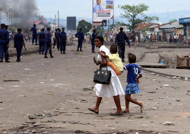 A family pass near Congolese riot police during a protest in Kinshasa, Democratic Republic of Congo, Monday, Sept. 19, 2016.