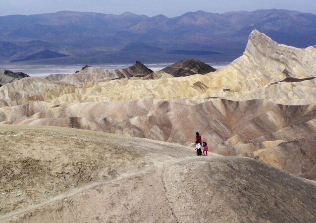 In this April 11,2010 file photo, tourists walk along a ridge at Death Valley National Park, Calif.