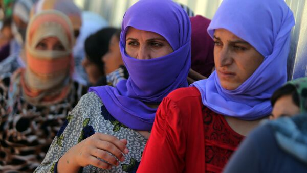 Yazidi Iraqi women queue in order to get food at the Bajid Kandala camp near the Tigris River, in Kurdistan's western Dohuk province, where they took refuge after fleeing advances by Islamic State jihadists in Iraq on August 13, 2014. (File) - Sputnik International