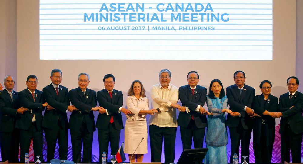 Canada's Foreign Minister Chrystia Freeland (C) links arms with ASEAN Foreign Ministers and their representatives as they take part in the ASEAN-Canada Ministerial Meeting of the 50th ASEAN Foreign Ministers' Meeting and its Dialogue Partners at the Philippine International Convention Center in Pasay city, metro Manila, Philippines