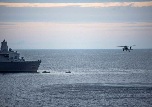 In this Saturday, Aug. 5, 2017, sailors man small boats as an MH-60S Sea Hawk helicopter, assigned to Helicopter Sea Combat Squadron (HSC) 25 flies overhead to recover personnel near the amphibious transport dock USS Green Bay (LPD 20) following an aviation mishap of an MV-22 Osprey, which caused the aircraft to enter the water off the coast of Australia.