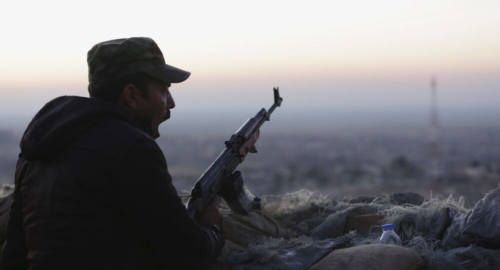 In this Friday, Nov. 13, 2015, file photo, a Kurdish fighter, known as a peshmerga, yawns as he stands guard on the frontline in Sinjar, Iraq