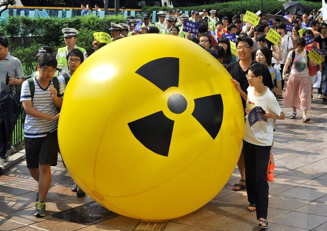 South Korean activists march while rolling a large balloon with a radioactivity warning sign during an anti-nuclear protest in Seoul on August 6, 2013 on the 68th anniversary of the atomic bombing of Hiroshima in Japan