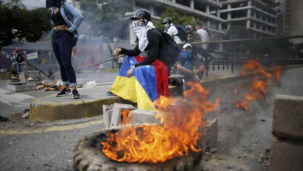 Masked anti-government demonstrators stend to a burning barricade during a protest against the installation of a constitutional assembly in Caracas, Venezuela, Friday, Aug. 4, 2017 - Sputnik International