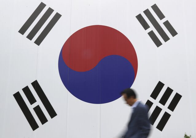A man walks by a huge national flag printed on the wall in Seoul, South Korea, Wednesday, Oct. 26, 2016