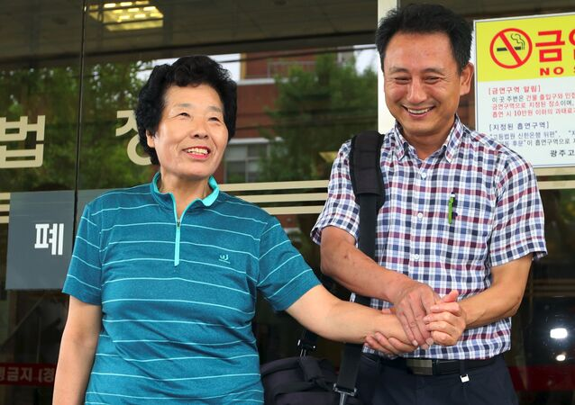 Lee Kyung-Ja (L), a relative of late victim Choe Jeong-Rye, and Lee Kuk-Un (R), who leads a group of activists working for former slave workers, react outside the district court in the southern city of Gwangju on August 8, 2017 after the court ruled Mitsubishi Heavy Industries should pay compensation to two South Korean former wartime slave workers