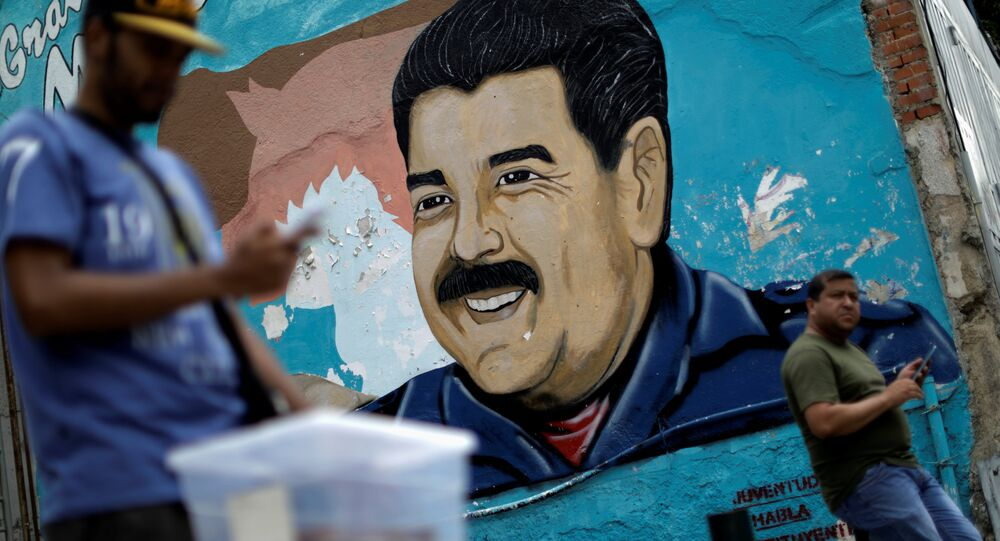 A man walks past a portrait of Venezuela's President Nicolas Maduro in Caracas, Venezuela August 7, 2017.