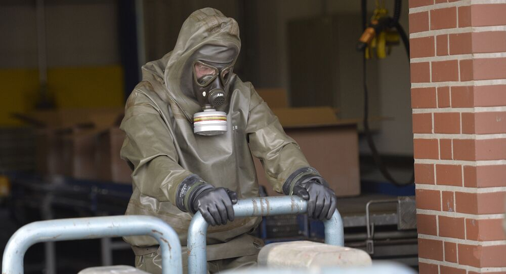 An expert in protective gear shows the disposal of chemical weapons during a media day at the German state-run company GEKA, specialized in the disposal of hazardous materials in Munster, northern Germany, Wednesday, March 5, 2014