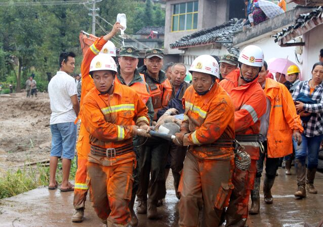 Rescue workers carry an injured villager at the site of a landslide that occurred in Gengdi village, Puge county, Sichuan province, China August 8, 2017