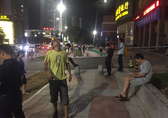 People stand outside buildings after an earthquake was felt in Xian in central China's Shanxi province on August 8, 2017