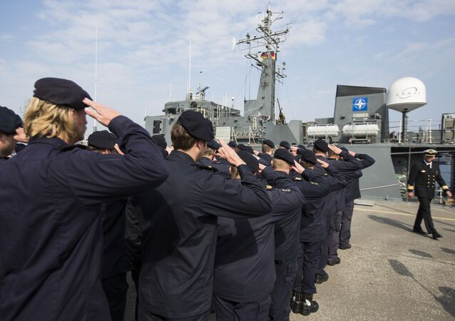 Crew members of Norwegian minesweeper Otra salute after a briefing of NATO Allied Maritime Command Deputy Chief of Staff for Operations, Commodore Arian Minderhoud, right, of the Royal Netherlands Navy before setting sail together in a convoy of five ships of Norway, Belgium, the Netherlands and Estonia from Kiel, Germany, Tuesday, April 22, 2014