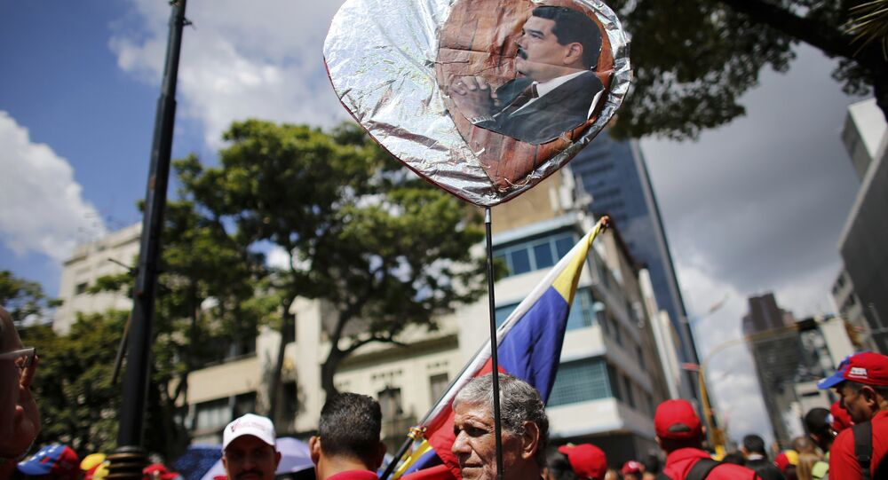 A government supporter holds a heart-shaped placard decorated with an image of Venezuela's Nicolas Maduro during a rally in support of the Constitutional Assembly outside of the National Assembly building in Caracas, Venezuela, Monday, Aug. 7, 2017.