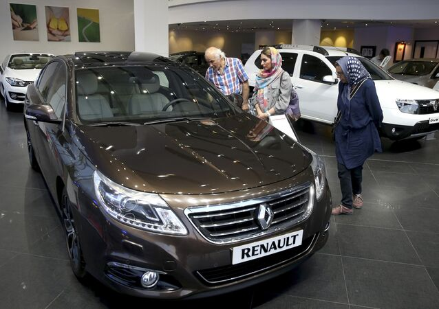 In this Thursday, July 16, 2015 photo, Iranians look at a Renault sedan at a dealership in northern Tehran, Iran