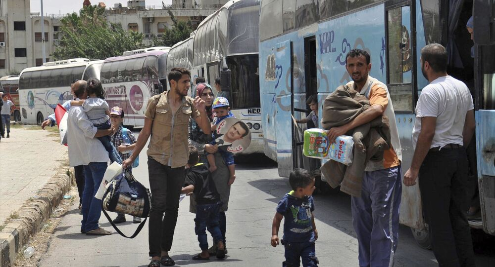 This photo released Tuesday, July 11, 2017 by the Syrian official news agency SANA, shows Syrians arriving from Jarablus, in Aleppo province, to their old neighborhood of al-Waer, in Homs, Syria