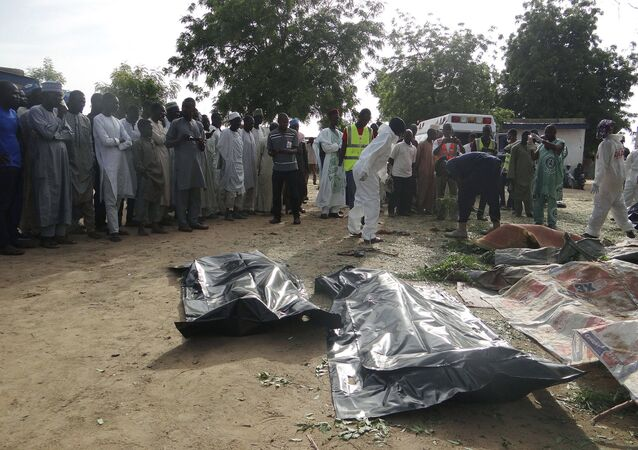 People mourn over the bodies of suicide bomb attack victims in a village near Maiduguri, Nigeria, Wednesday, July 12, 2017