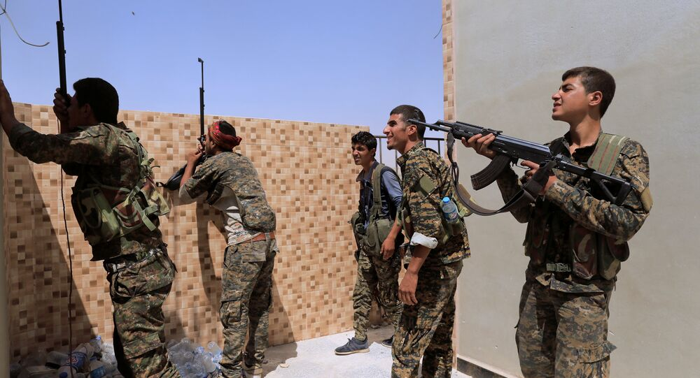 Members of the Syrian Democratic Forces try to locate Islamic State's sniper in Al Senaa, a district of Raqqa, Syria August 10, 2017