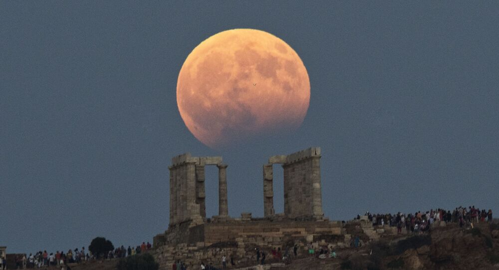 The August full moon rises above the 5th Century BC Temple of Poseidon at Cape Sounio, south of Athens, on Monday, Aug. 7, 2017.