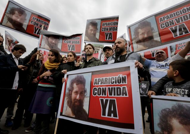"Relatives of Santiago Maldonado, including his brother German, center, and activists, hold photos of Maldonado and the Spanish message Appear alive now"" as they protest his disappearance outside Congress in Buenos Aires, Argentina, Monday, Aug. 7, 2017."