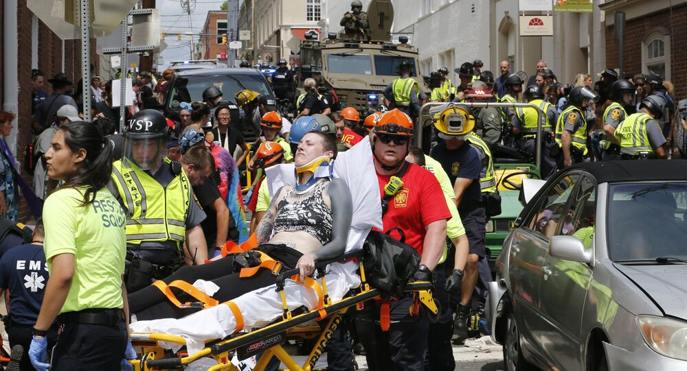 Rescue personnel help injured people after a car ran into a large group of protesters after a white nationalist rally in Charlottesville, Va., Saturday, Aug. 12, 2017.