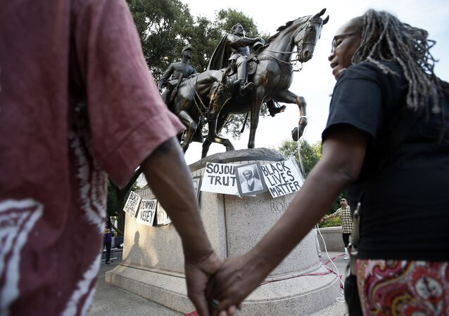 Activists gather around the Robert E Lee statute, erected to commemorate the Confederate Army General at Lee Park, chanting the names of Civil War era activists in Dallas. Lee was vilified during the Civil War only to become a heroic symbol of The Lost Cause and eventually a racist icon.
