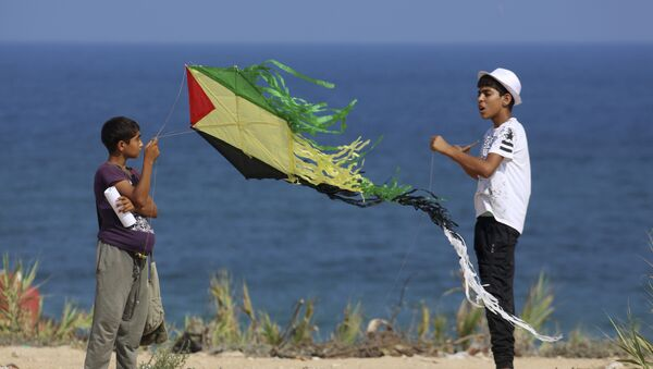 Palestinian youths fly their kites during a Hamas-sponsored summer scout camp, in an event held as a show of support against Israeli security measures installing metal detectors at the Al Aqsa Mosque compound in Jerusalem, on the beach near the Israeli border fence, in Beit Lahiya, northern Gaza Strip, Wednesday, July 19, 2017. - Sputnik International