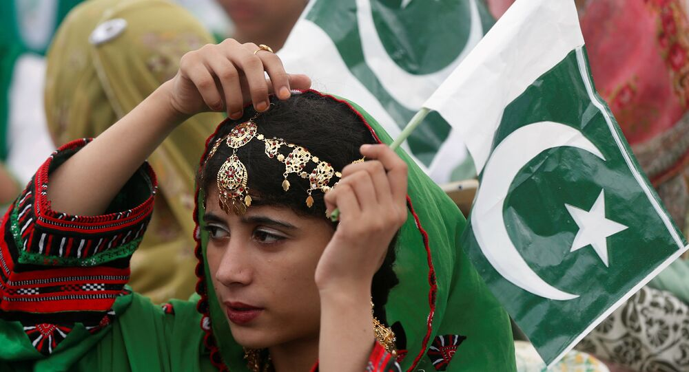 A girl holds a national flag as she attends a ceremony to celebrate Pakistan's 70th Independence Day at the mausoleum of Muhammad Ali Jinnah in Karachi, Pakistan August 14, 2017.