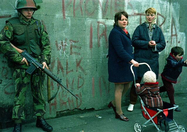 Women and children stand near an armed British military soldier patrols a street in Belfast, Northern Ireland, Feb. 1972. British paratroopers shot 13 demonstrators during a civil rights march on Jan. 30, known as Bloody Sunday.