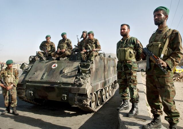 Afghan National Army soldiers stand near an armored military tank at a square in Kabul, Afghanistan on Tuesday, May 30, 2006.