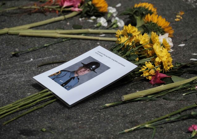 A photo of one of two Virginia state troopers killed in a helicopter crash lies among flowers at a makeshift memorial at the scene of where a car plowed into counter-protesters in Charlottesville, Virginia