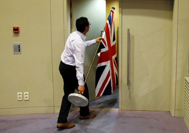 An official carries a Union Jack flag ahead of a news conference by Britain's Secretary of State for Exiting the European Union David Davis and European Union's chief Brexit negotiator Michel Barnier in Brussels, Belgium July 20, 2017