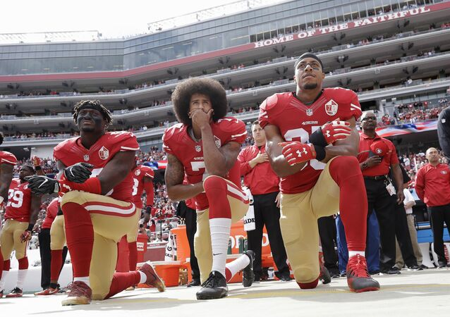 In this Oct. 2, 2016 file photo, from left, San Francisco 49ers outside linebacker Eli Harold, quarterback Colin Kaepernick and safety Eric Reid kneel during the national anthem before an NFL football game against the Dallas Cowboys in Santa Clara, Calif.