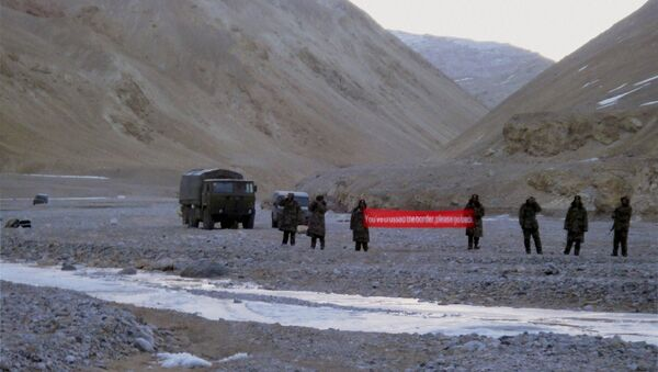(File) In this May 5, 2013 file photo, Chinese troop hold a banner which reads, You've crossed the border, please go back, in Ladakh, India - Sputnik International