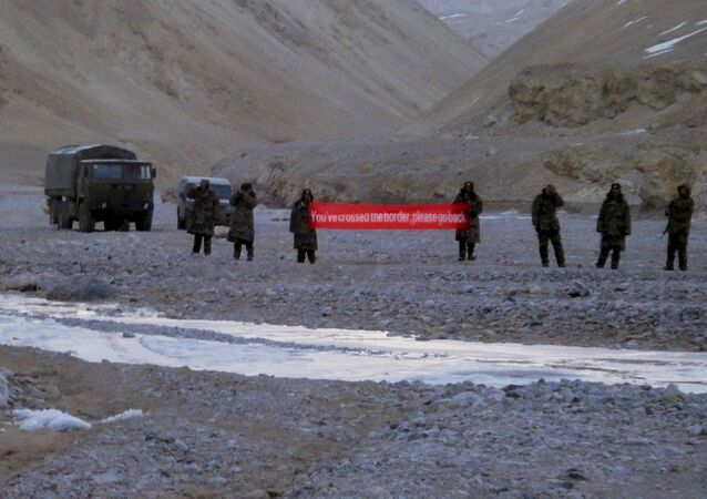 (File) In this May 5, 2013 file photo, Chinese troop hold a banner which reads, You've crossed the border, please go back, in Ladakh, India