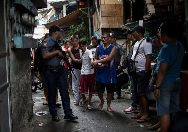 Male residents are rounded up for verification after police officers conducted a large scale anti-drug raid at a slum community in Manila on July 20, 2017