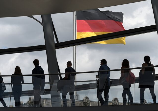 Visitors walk in the glass cupola of the Reichstag building that hosts the German parliament (Bundestag) and look at a German flag in Berlin, Germany, on June 10, 2016.