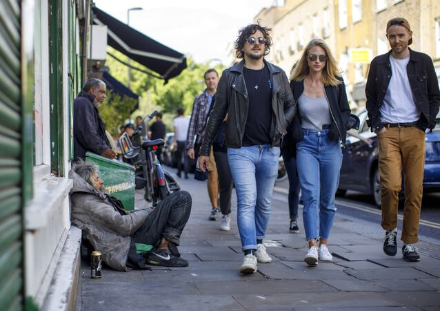 A group of people walks past homeless people on Broadway Market in east London on July 23, 2017