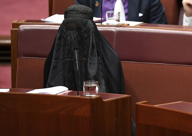 Sen. Pauline Hanson, bottom left, wears a burqa during question time in the Senate chamber at Parliament House in Canberra, Australia, Thursday, Aug. 17, 2017.