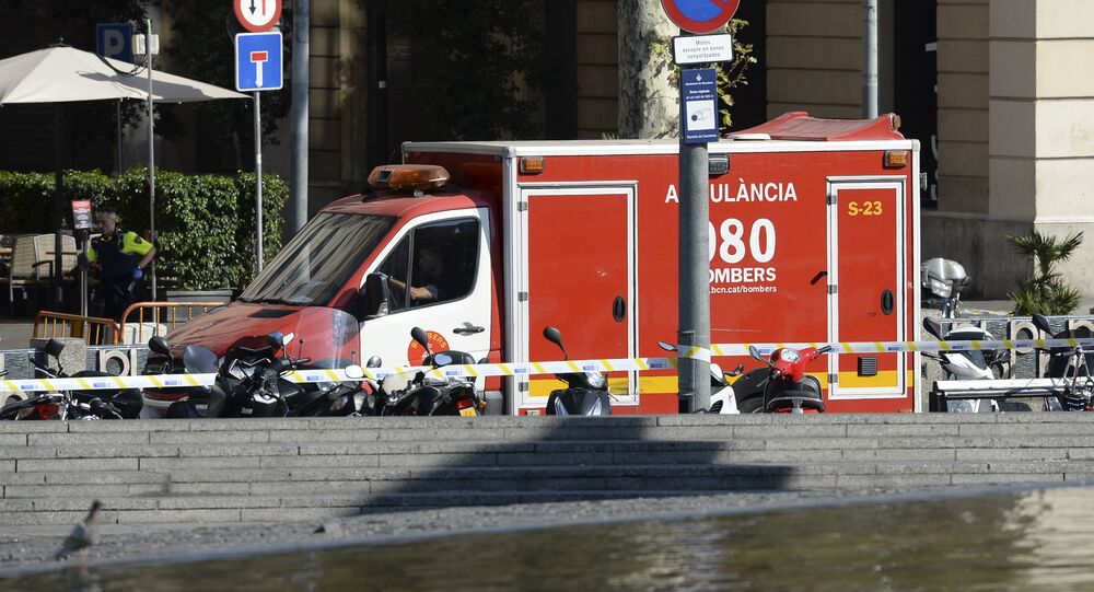 A policeman stands next to an ambulance after a van ploughed into the crowd, injuring several persons on the Rambla in Barcelona on August 17, 2017