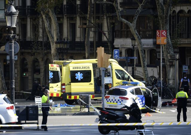A policemen and a medical staff member stand past police cars and an ambulance in a cordoned off area after a van ploughed into the crowd, injuring several persons on the Rambla in Barcelona on August 17, 2017