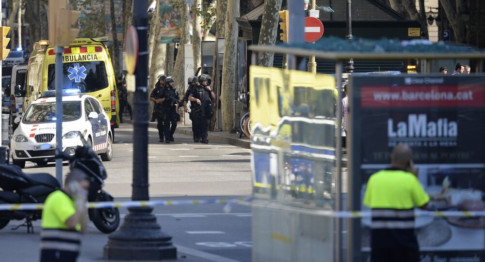 Armed policemen arrive in a cordoned off area after a van ploughed into the crowd, injuring several persons on the Rambla in Barcelona on August 17, 2017