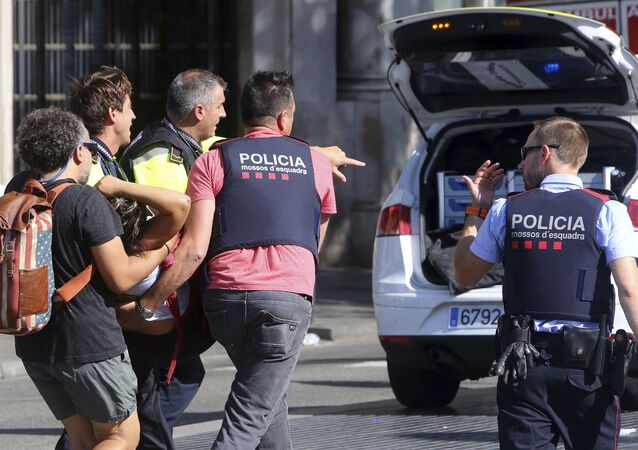 An injured person is carried in Barcelona, Spain, Thursday, Aug. 17, 2017, after a white van jumped the sidewalk in the historic Las Ramblas district, crashing into a summer crowd of residents and tourists and injuring several people, police said