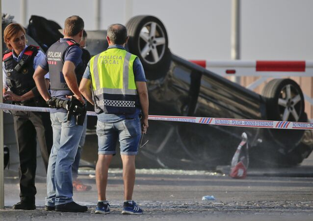 Police officers stand near an overturned car onto a platform at the spot where terrorists were intercepted by police in Cambrils, Spain, Friday, Aug. 18, 2017