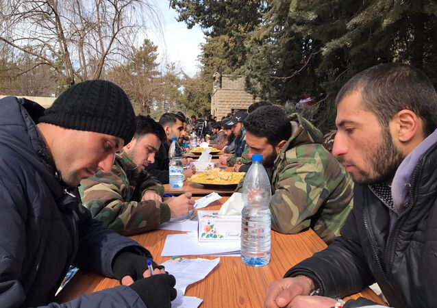 Militants hand in personal weapons to Syrian army representatives as part of the people's reconciliation program. File photo