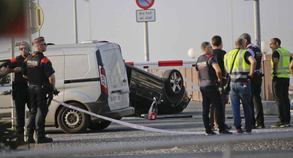A police officer walks near an overturned car at the spot where terrorists were intercepted by police in Cambrils, Spain, Friday, Aug. 18, 2017