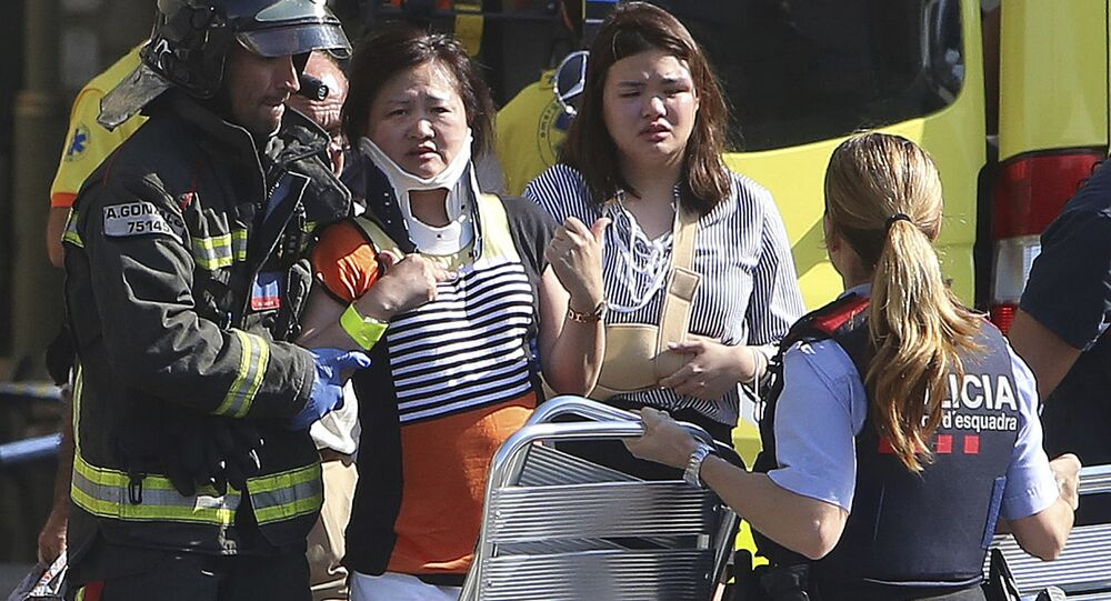 Injured people are treated in Barcelona, Spain, Thursday, Aug. 17, 2017 after a white van jumped the sidewalk in the historic Las Ramblas district, crashing into a summer crowd of residents and tourists and injuring several people, police said