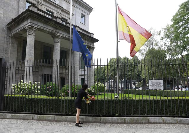 The Spanish and the European flag fly at half mast as a woman fixes flowers at the fence of the Spanish embassy in Berlin, on August 18, 2017 in tribute to victims of the Barcelona attack