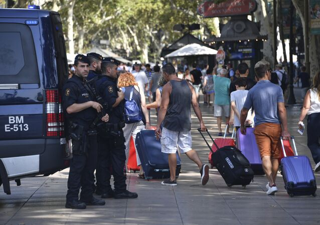 Spanish policemen stand guard as tourists pass by with their suitcases on the Rambla boulevard on August 18, 2017