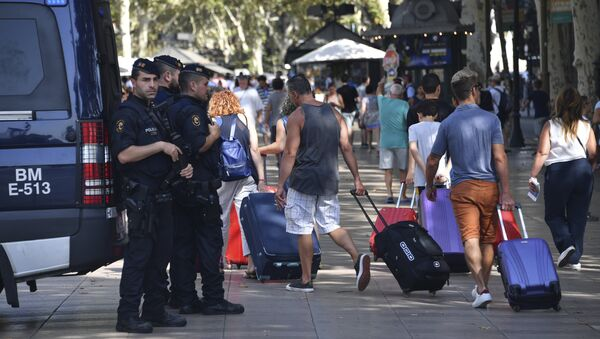 Spanish policemen stand guard as tourists pass by with their suitcases on the Rambla boulevard on August 18, 2017 - Sputnik International